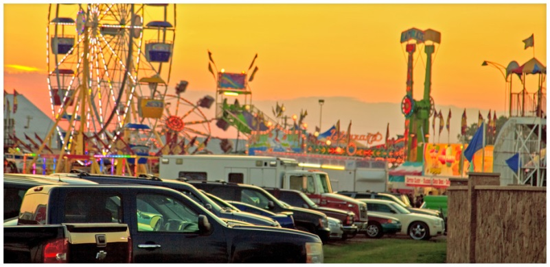Vehicles parked in front of the fair amusement rides